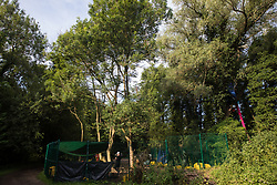 Denham, UK. 26 June, 2020. A HS2 security guard stands together in a compound in Denham Country Park from which woodland is being cleared for the HS2 high-speed rail link.