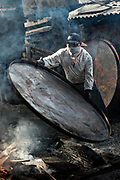 A indigenous Purepecha worker places a copper pan on an open forge to begin the process of hardening and forming the pan at a copper workshop in Santa Clara del Cobre, Michoacan, Mexico. The Purepecha people have been crafting copper crafts since the 12th century.