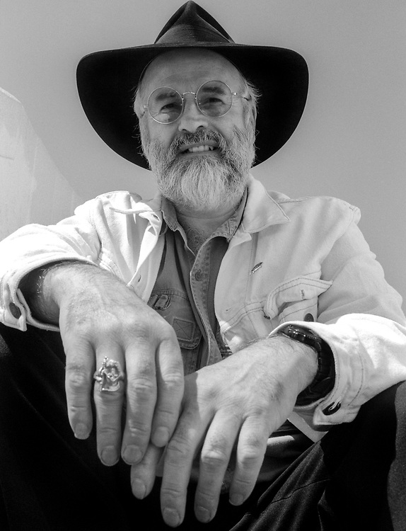 """Sir Terry Pratchett is among the top fantasy writers of the last century and Britain's most shoplifted novelist! He was Britain's best selling author in the 1990s until J K Rowling arrived. I photographed Terry in 1996 for a leading newspaper as he was at his peak. I knew little of him. He was a well know fantasy novelist – a genre I never fancied, I'm afraid!  I am not sure I knew he had a proclivity for wearing large, black fedora hats beforehand either!<br /> <br /> He was a delight to photograph, but as with most newspapers, it was in/out and back to the picture desk with the images! I squeezed out a single roll of b/w! His style was recognized as more """"urban cowboy than city gent"""" and when asked if he ever took his hat off, he replied: """"I do take it off sometimes because how else is a man to shower?"""""""