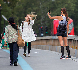 © Licensed to London News Pictures. 21/08/2020. London, UK. Commuters on Westminster Bridge this morning as strong winds hit London and the South East today. Storm Ellen continues to batter the UK with winds in excess of 40mph as the Met Office issue a yellow weather warning for high winds for Friday which could lead to travel and power disruption. Photo credit: Alex Lentati/LNP