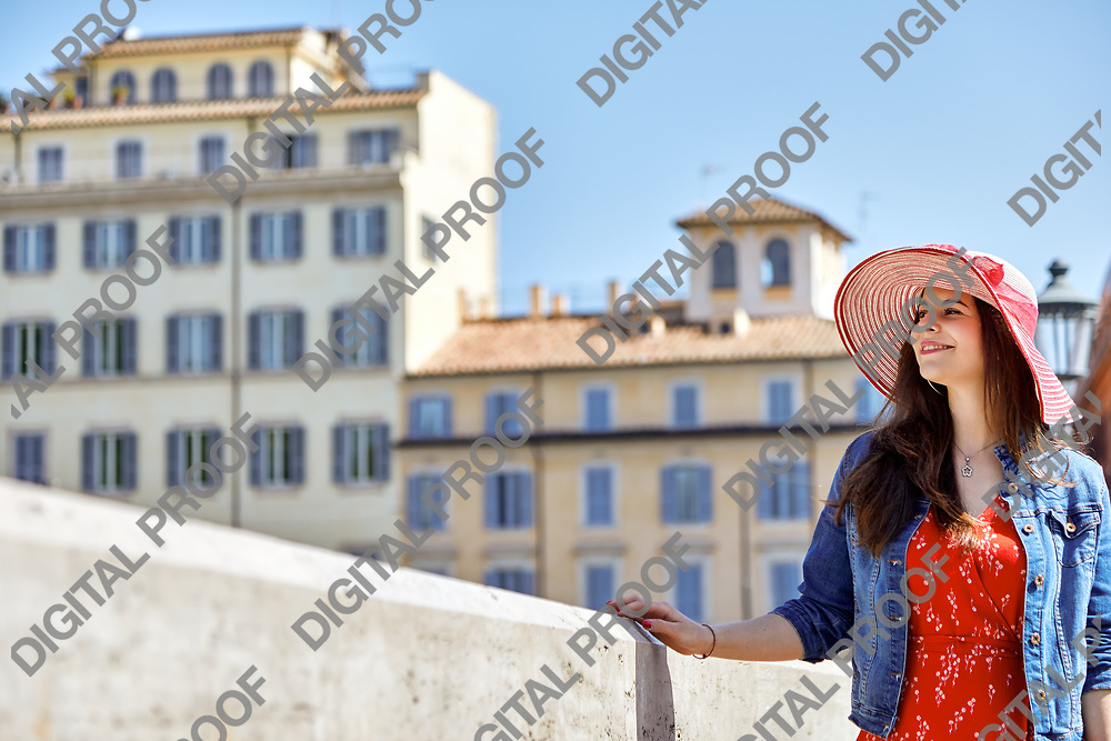 Cheerful tourist woman touching handrail and standing on sunny old town street.