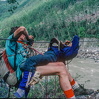 Gordon Wiltsie photographs a vaillager crossing a cable bridge over the Po Tsangpo River in the Tsangpo Gorge of eastern Tibet, China, one of the world's deepest canyons.