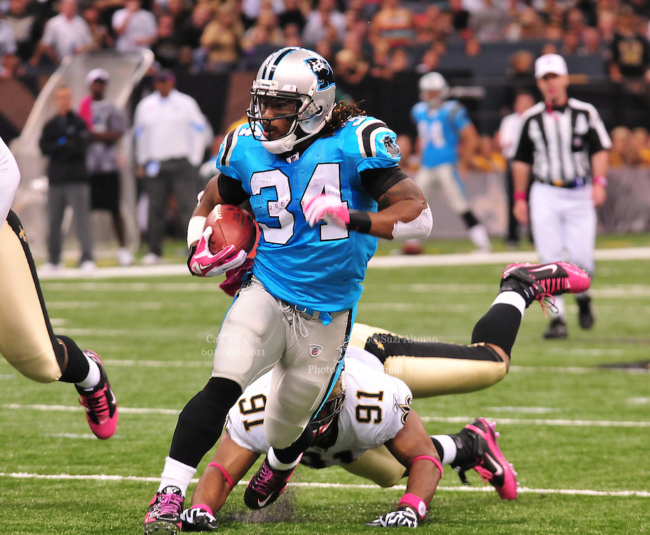 """Carolina Panthers RB DeAngelo Williams 34 breaks a tackle from New Orleans Saints Will Smith 91 and score a touchdown Sunday Oct. 3,2010. The NFL has gone """"Pink"""" for October in honor of Breast Cancer Awareness. The Saints went on to win 16-14. John Carney kicked three field goals to help the Saints win. PHOTO©SuziAltman.com"""
