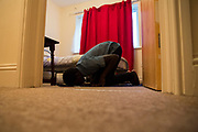 An unaccompanied minor refugee child praying on the floor in his bedroom where he has been recently housed. United Kingdom (photo by Andrew Aitchison / In pictures via Getty Images)