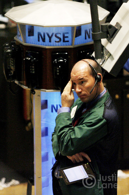 A trader rubs his forehead while on the floor of the New York Stock Exchange at the end of trading in New York, New York on Tuesday 27 February 2007. The Dow Jones Industrial average ended down 416 points, or 3 percent,  after China's equity market tumbled today.