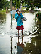 30 SEPTEMBER 2016 - SAI NOI, AYUTTHAYA, THAILAND:  A man walks through the flooded Wat Boonkannawas in Sai Noi. The Chao Phraya River, the largest river that runs through central Thailand, has hit flood stage in several areas in Ayutthaya and Ang Thong provinces. Villages along the river are flooded and farms are losing their crops due to the flood. This is the same area that was devastated by floods in 2011, but the floods this year are not expected to be as severe. The floods are being fed by water released from upstream dams. The water is being released to make room for heavy rains expected in October.     PHOTO BY JACK KURTZ
