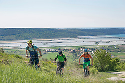 Bikers moving up through grass and houses and lakes in background