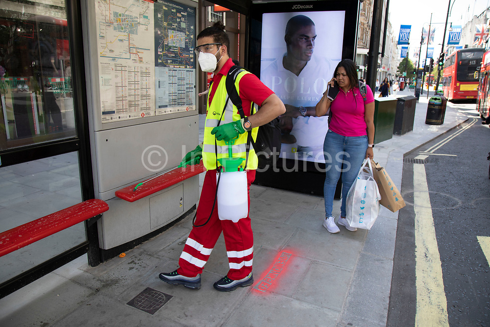 Worker disinfects the areas which people regulalrly touch with their hands such as this bus stop along Oxford Street as the Coronavirus lockdown measures are set to ease further, the west end starts to fill with people as they return to the shopping district and the quiet city starts coming to an end on 22nd June 2020 in London, England, United Kingdom. As of today the government has relaxed its lockdown rules, and is allowing some non-essential shops to open with individual shops setting up social distancing queueing systems.