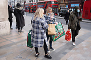 Disneystore shopping bags as the national lockdown ends and the new three tier system of local coronavirus restrictions begins, shoppers head out to Oxford Street to catch up on shopping as non-essential shops are allowed to reopen on 2nd December 2020 in London, United Kingdom. Many shoppers wear face masks outside on the street as a precaution as there are so many people around.