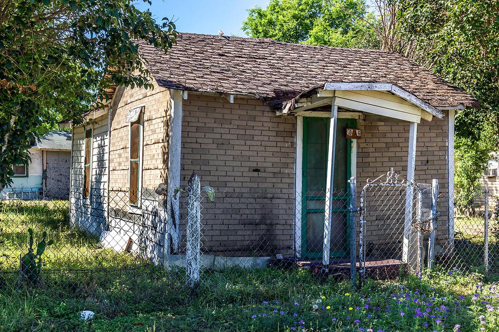 Run down small brick home in a poor run down neighbourhood of Hondo, TX