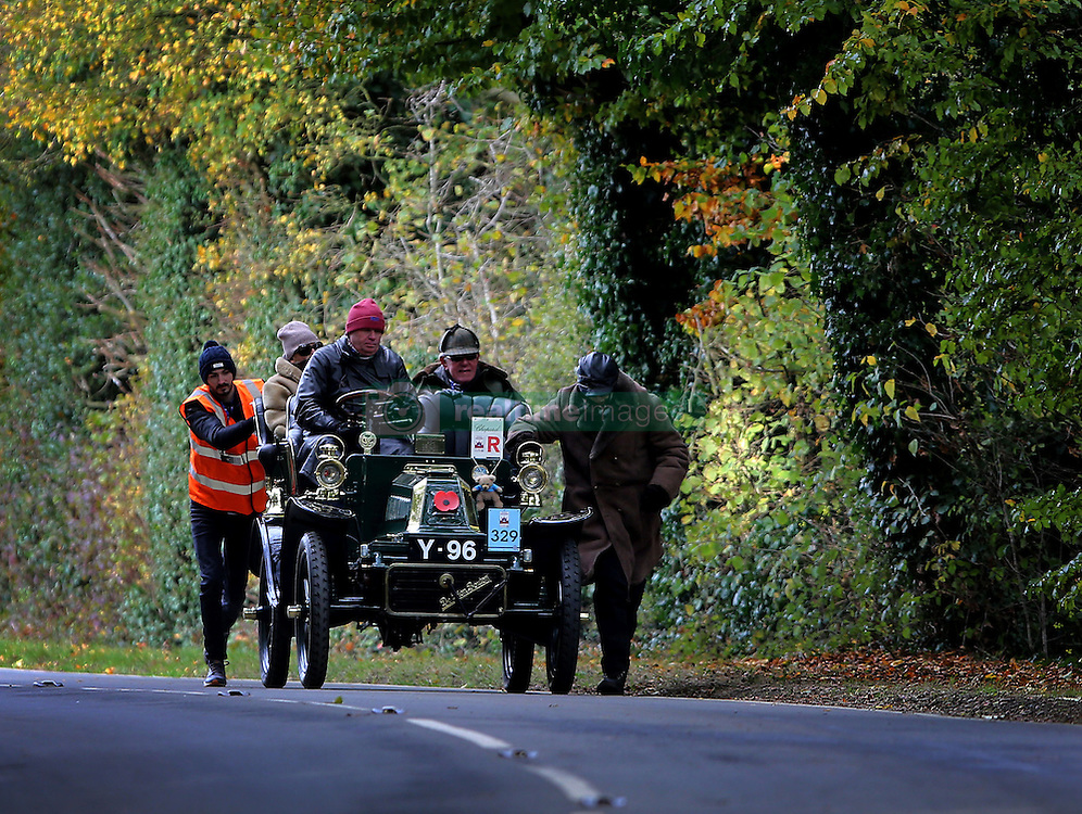 Participants in the Bonhams London to Brighton Veteran Car Run are helped up Holmsted Hill near Crawley, Sussex.