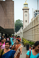 Women smile as they leave the building after finishing a day's work at the Central Bank of Sri Lanka in Colombo, Sri Lanka. The Old Colombo Lighthouse and clock tower, completed in 1857, is in the background. (March 29, 2017)
