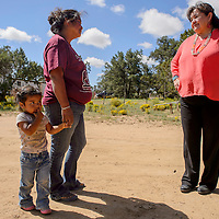 Marlena Garcia and her daughter Kaylee Jake talk with Peacemakers manager Ruby Holstein, right, at Garcia's home in Pinehill August 31.