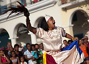 Cuban young woman girl of African descent dancing, and waving a stick  and shouting, as part of a performance. Performance in Havana old town, local dance and theatre group enacting the slave trade, colonial rule and how African religion and beliefs continuing, becoming what is now Santeria.