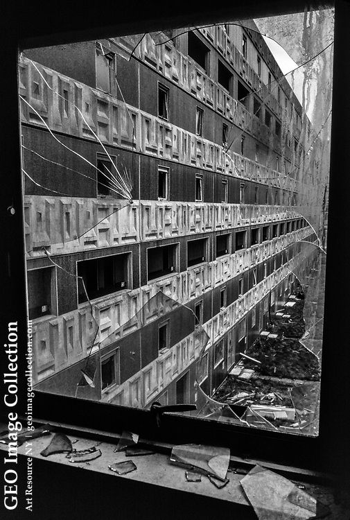 Decaying, condemned and vacant tenement public housing project in the Gorbals district, Glasgow, Scotland.  The empty council housing apartment blocks were built in the 1960s to replace notorious gritty slum neighborhoods of Glasgow and improve derelict working class housing. However, the buildings developed extreme dampness and mold that made the flats uninhabitable within a few years. The neighborhood was associated with disrepair, unemployment, violence, gang culture, and youth gangs. Parts of the Gorbals have been redeveloped.
