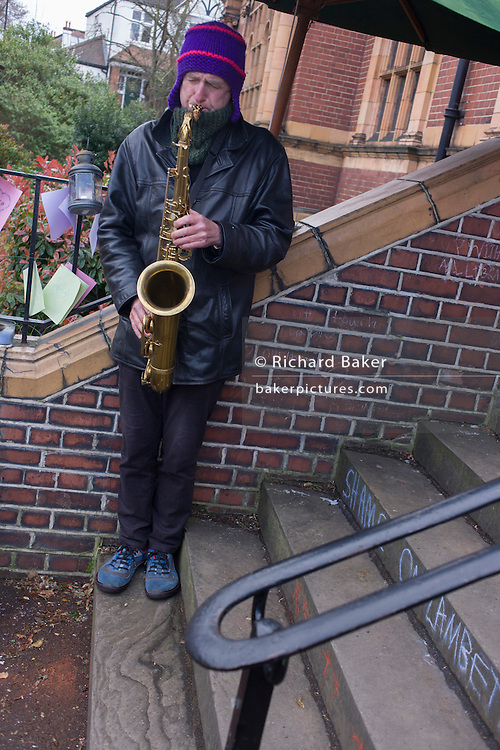 A local musician plays the saxophone outside Carnegie Library in Herne Hill, south London while occupiers remain inside the premises on day 7 of its occupation, 6th April 2016. The angry local community in the south London borough have occupied their important resource for learning and social hub for the weekend. After a long campaign by locals, Lambeth have gone ahead and closed the library's doors for the last time because they say, cuts to their budget mean millions must be saved.