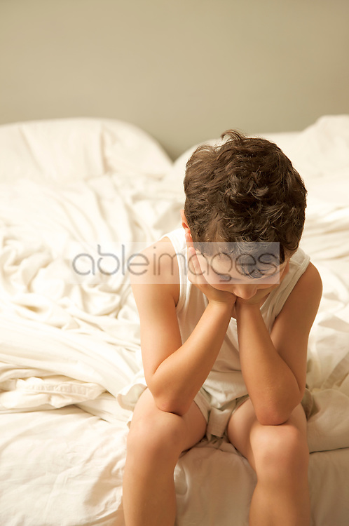 Young boy sitting on the end of a bed with face resting on hands