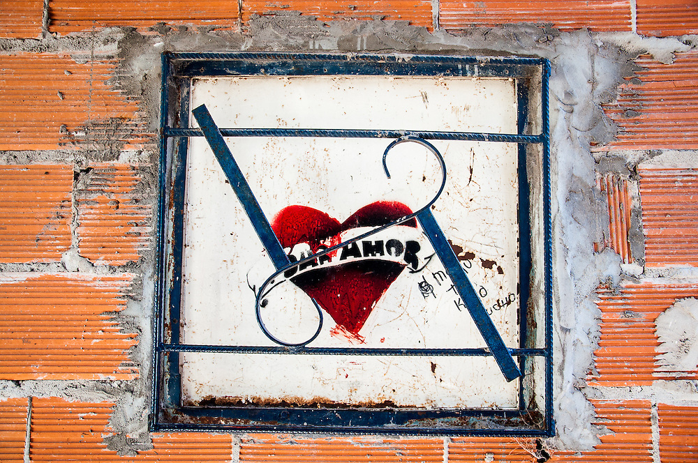 """2015, Buenos Aires, Argentina. View of a boarded window painted with a heart-shaped graffiti that states """"Dar Amor"""" (give love) in one of the passageways of the slum."""