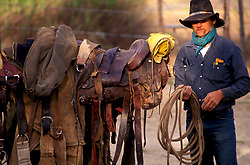 man in a cowboy hat prepaing ropes and saddles in the morning
