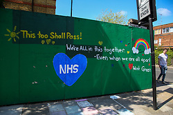 © Licensed to London News Pictures. 25/04/2020. London, UK. A man walks past a 'THIS TOO SHALL PASS!. WE'RE ALL IN THIS TOGETHER. EVEN WHEN WE ARE ALL APART' sign in Tottenham during coronavirus lockdown.<br /> The lockdown continues to slow the spread of COVID-19 and reduce pressure on the NHS.  Photo credit: Dinendra Haria/LNP
