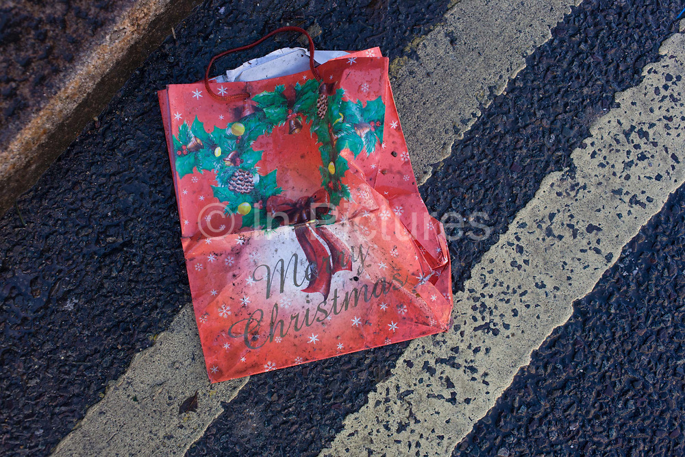 A dropped bag with a Merry Christmas message in a south London gutter. Xmas is over, the decorations are down and the city returns to the grim grind on a January winter day. The discarded bag symbolises the end of merriment and joy, an unhappy reminder of the good times and optimism. Diagonal lines from double-yellow (no) parking lines cross the picture that suggests a memory of better times.