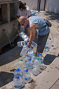 Using recycled bottles, locals collect thermal spring water at Fonte de Sao Joao, on 17th July 2016, in the spa resort of Luso, Portugal. In the 11th century, Luso was a sleepy village linked to a monastery in the hills near Coimbra but it became a lively spa resort in the 1700s as its hot water springs became a focus for tourism. The waters here are said to have therapeutic value in the treatment for bad circulation, muscle tone, rheumatism and renal problems. (Photo by Richard Baker / In Pictures via Getty Images)