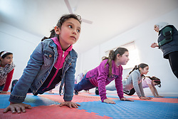17 February 2020, Zarqa, Jordan: A group of girls do push-ups during a Zumba session for children at the Lutheran World Federation community centre in Zarqa. Through a variety of activities, the Lutheran World Federation community centre in Zarqa serves to offer psychosocial support and strengthen social cohesion between Syrian, Iraqi and other refugees in Jordan and their host communities.