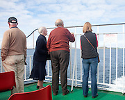 People looking back to the island from a Caledonian MacBrayne ferry ship leaving Barra, Outer Hebrides, Scotland, UK