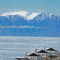 Houses in Pond Inlet rise above the shore of Lancaster Sound, north of Baffin Island, Nunavut, Canada.  Behind are mountains on Bylot Island.