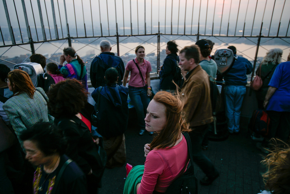 Visitors look at the view of Manhattan buildings  from the Empire State Building viewing deck.