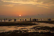 People paddle in the sea and walk along the sandy shoreline of Laboni Beach looking out to the Bay of Bengal in Cox Bazar,  Chittagong Division, Bangladesh, Asia.  The sunlight is reflected on the wet sand.  This is part of the coastline which is claimed to be the longest natural sea sandy beach in the world, running 120 kilometers.  (photo by Andrew Aitchison / In pictures via Getty Images)