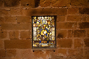 Lay Brothers Dormitory and contemporary stained glass windows at Fontfroide Abbey near Narbonne, France. Fontfroide Abbey is a former Cistercian monastery in France, situated 15 kilometers south-west of Narbonne. It was founded in 1093 by Aimery I, Viscount of Narbonne, but remained poor and obscure, and needed to be refounded by Ermengarde, Viscountess of Narbonne. The abbey fought together with Pope Innocent III against the heretical doctrine of the Cathars who lived in the region. It was dissolved in 1791 in the course of the French Revolution. The premises, which are of very great architectural interest, passed into private hands in 1908, when the artists Gustave and Madeleine Fayet dAndoque bought it to protect the fabric of the buildings from an American collector of sculpture. They restored it over a number of years and used it as a centre for artistic projects. It still remains in private hands. Today it is open to paying guests.
