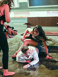 © Licensed to London News Pictures . 01/01/2014 . Manchester , UK . A man and a woman fall to the ground outside Manchester's Printworks club venue . Revellers see in the New Year in Manchester today (January 1st 2014) as police report that officers are at full stretch responding to calls . Photo credit : Joel Goodman/LNP