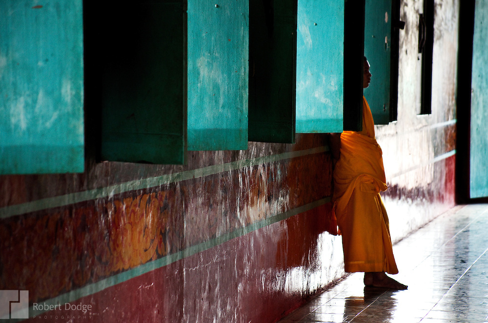 A Buddhist monk stands behind a window shutter at a monastery in Soc Trang Province. Robert Dodge, a Washington DC photographer and writer, has been working on his Vietnam 40 Years Later project since 2005. The project has taken him throughout Vietnam, including Hanoi, Ho Chi Minh City (Saigon), Nha Trang, Mue Nie, Phan Thiet, the Mekong, Sapa, Ninh Binh and the Perfume Pagoda. His images capture scenes and people from women in conical hats planting rice along the Red River in the north to men and women working in the floating markets on the Mekong River and its tributaries. Robert's project also captures the traditions of ancient Asia in the rural markets, Buddhist Monasteries and the celebrations around Tet, the Lunar New Year. Also to be found are images of the emerging modern Vietnam, such as young people eating and drinking and embracing the fashions and music of the West. His book. Vietnam 40 Years Later, was published March 2014 by Damiani Editore of Italy.