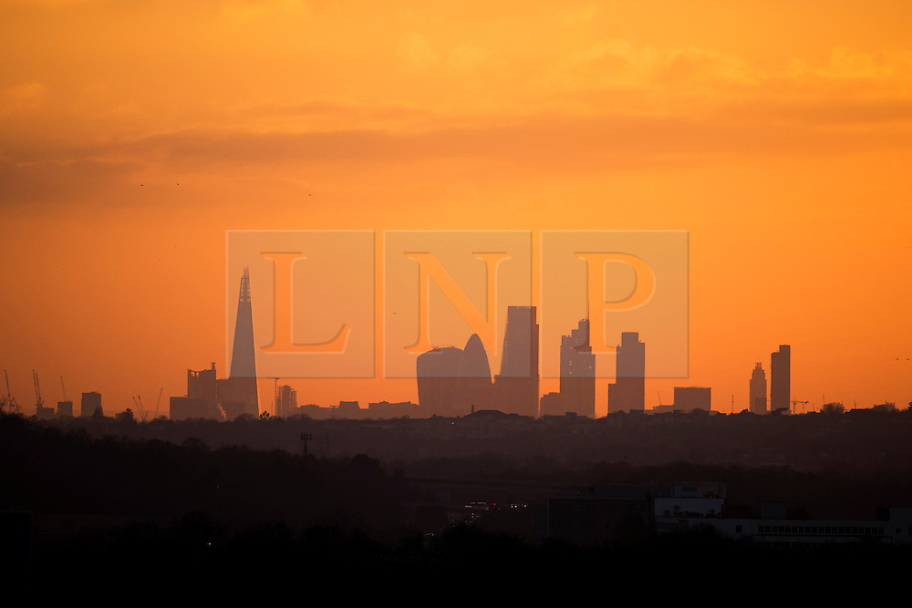 © Licensed to London News Pictures. Sunset over the skyline of London, seen from the M11 in Essex on December 28, 2014. Photo credit : Ben Cawthra/LNP