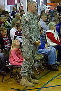 Westfall, Pennsylvania - A Delaware Valley  Elementary School student looks up at her father, who is wearing his Army uniform, at an assembly in the gymnasium where veterans were honored on Nov. 8, 2013.