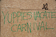 Anti gentrification graffiti reads Yuppies Vacate Carnival on a boarded up property during carnival in Notting Hill in London, England, United Kingdom.