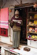 Man reading a newspaper early morning, Varanasi, India