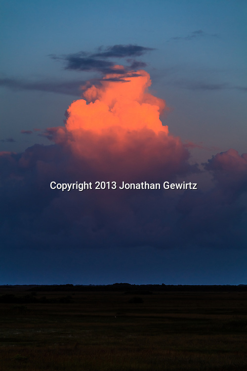 The last rays of the setting sun illuminate towering cumulus clouds over sawgrass prairie in the Shark Valley section of Everglades National Park, Florida. <br /> <br /> WATERMARKS WILL NOT APPEAR ON PRINTS OR LICENSED IMAGES.<br /> <br /> Licensing: https://tandemstock.com/assets/42849830
