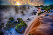 "Iguazu Falls, Iguazú Falls, Iguassu Falls or Iguaçu Falls are waterfalls of the Iguazu River on the border of the Argentine province of Misiones and the Brazilian state of Paraná. The falls divide the river into the upper and lower Iguazu. The Iguazu River rises near the city of Curitiba. The river flows through Brazil for most of its course, although most of the falls are on the Argentine side. Below its confluence with the San Antonio River, the Iguazu River forms the boundary between Argentina and Brazil.<br /> The name ""Iguazu"" comes from the Guarani or Tupi words ""y"", meaning ""water"", and ""ûasú "", meaning ""big"". Legend has it that a god planned to marry a beautiful woman named Naipí, who fled with her mortal lover Tarobá in a canoe. In rage, the god sliced the river, creating the waterfalls and condemning the lovers to an eternal fall. The first European to find the falls was the Spanish conquistador Álvar Núñez Cabeza de Vaca in 1541."