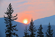 Sun setting over the Rocky Mountains with heavy fire smoke in the air<br /> Kootenay Plains on the David Thompson Highway<br /> Alberta<br /> Canada