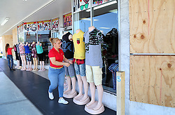 """As neighbor stores remained boarded up, Youlani Garcia, right, and her daughter Thalia Padron, set up mannequins with clothing for sale at their fashion store, """"El Cadalzo,"""" in Miami after Hurricane Irma passed over South Florida, on Tuesday, September 12, 2017. Photo by Pedro Portal/El Nuevo Herald/TNS/ABACAPRESS.COM"""