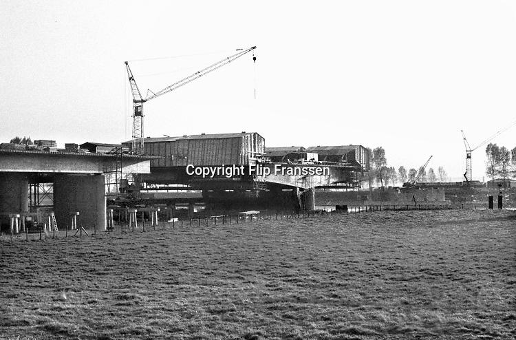 Nederland, Wijchen, 15-2-1974 Aanleg van de snelweg A50 tussen Arnhem en Oss . Bij Niftrik wordt gebouwd aan de brug over de Maas naar Ravenstein . Later werd de weg uitgebreid en ging van Zwolle tot Eindhoven Foto: Flip Franssen