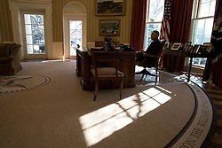 Sun streams in the window as President Barack Obama sits at the Resolute Desk in the Oval Office, Feb. 17, 2015. (Official White House Photo by Pete Souza)<br /> <br /> This official White House photograph is being made available only for publication by news organizations and/or for personal use printing by the subject(s) of the photograph. The photograph may not be manipulated in any way and may not be used in commercial or political materials, advertisements, emails, products, promotions that in any way suggests approval or endorsement of the President, the First Family, or the White House.