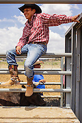 14 JULY 2012 - OAK SPRINGS, AZ: A cowboy leans against the chutes during bull riding classes in Oak Springs, AZ, Saturday. The bull riding class was offered by the Crooked Horn Cattle Co. in the community of Oak Springs on the Navajo Nation, about 15 miles south of Window Rock, AZ. Eleven cowboys signed up for bull riding classes and one signed up for bull fighting classes. The bull riding class started with lessons on a mechanical bucking machine before the cowboys rode bulls.    PHOTO BY JACK KURTZ