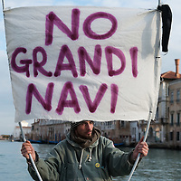 "VENICE, ITALY - JANUARY 16:  A protester sailing on the Grand Canal holds black listed banner reading ""Stop the large Ships""  on the day of the special meeting discussing the environmental impact of cruises in Venice on January 16, 2012 in Venice, Italy. Protest are mounting in Venice against large cruise ships crossing St Marks's basin after the Costa Concordia tragedy."