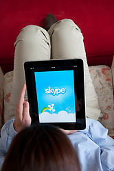 Woman using iPad tablet computer to use internet telephone service Skype online