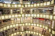 Interior view showing the floor levels of the mall's atrium and shoppers at Joy City shopping mall. Xidan is one of the main commercial shopping area in the Xicheng district of Beijing, China. With Joy City as it's centerpiece, a 13-story complex of western and Chinese shops. This is a shoppers haven as modern consumerism and commerce have a strong grip on Beijing's shop hungry crowds.