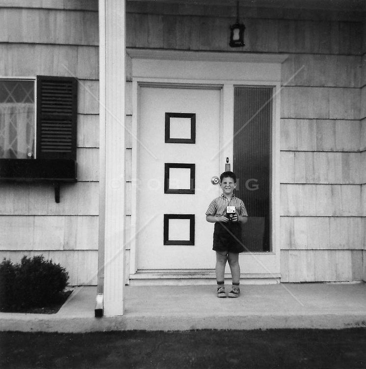 boy holding a kodak camera in front of a house