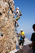 Climbers ascend a via ferrata route ladder above Rifugio Lorenzi on Monte Cristallo, in the Dolomites, Italy, Europe. Monte Cristallo lies within Parco Naturale delle Dolomiti d'Ampezzo, in the Ampezzo Dolomites, part of the Southern Limestone Alps. A lift to Forcella Staunies on Monte Cristallo gives unforgettable views over the mountains near Cortina d'Ampezzo. Directions: From Cortina, drive 6km east on SR48 to the large parking lot for Ski Area Faloria Cristallo Mietres (just west of Passo Tre Croci Federavecchia). Take a chair-lift from Rio Gere to Son Forca (rising from 1698m to 2215m). Then take the old style ovovia (egg-shaped) Gondellift Forcella Staunies to Rifugio Guido Lorenzi (2932m) for astounding deck views and exciting via ferrata climbing routes. UNESCO honored the Dolomites as a natural World Heritage Site in 2009.